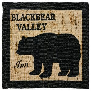 Camp Nature Trails Table Mat. Nostalgic keepsake remake of 1930's Camp Decor with wildlife stamp patterns. Black bear icon on faux wood background with black border. Cotton and canvas. 13″ X 13″