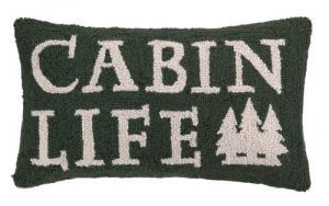 "Cabin Life Pillow. Dark forest green hooked pillow announces ""Cabin Life"" with three interlocking pines highlighting the pillow. 12″ x 22"